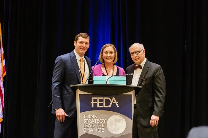 Woman accepts award from FEDA guys