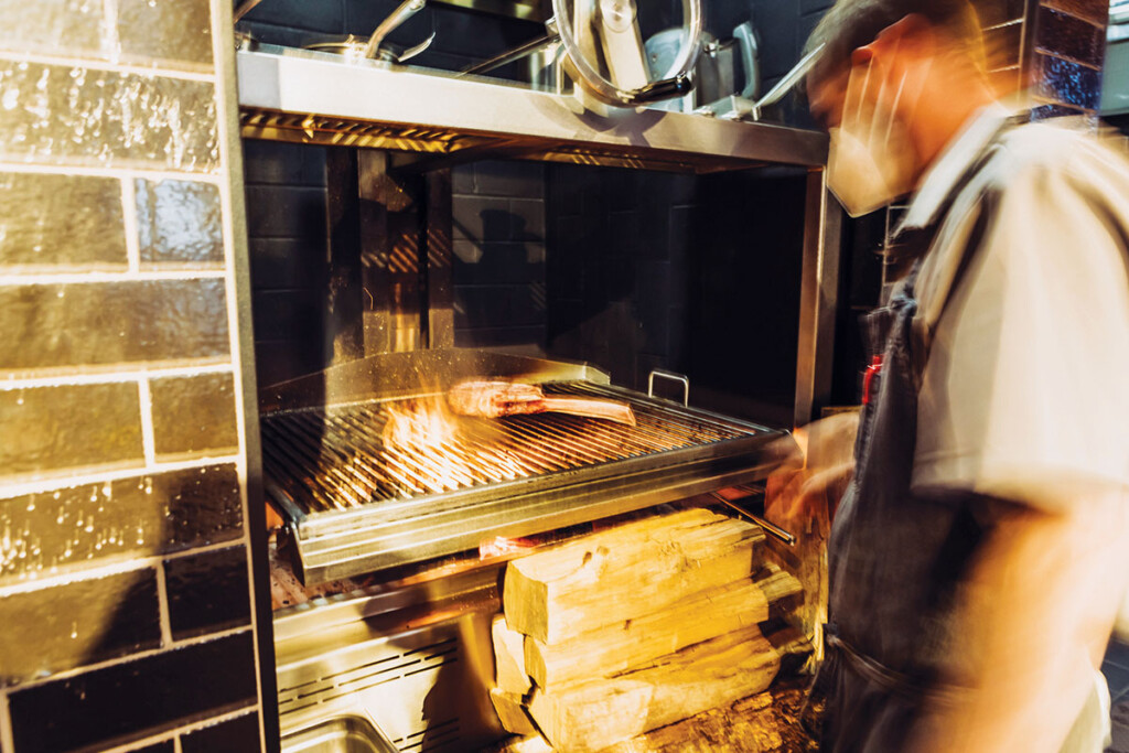 A wood-fired charbroiler serves as the heart of the tavern's cookline. Its control wheel and counterweights allow cooks to raise and lower the grill as needed.